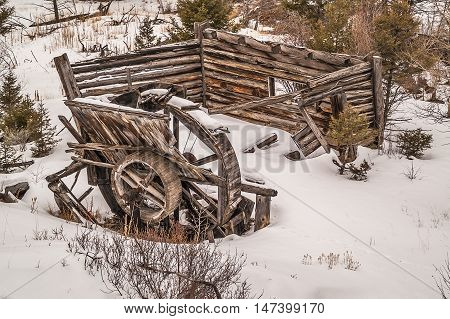 Broken water wheel and falling down log building are part of an old homestead