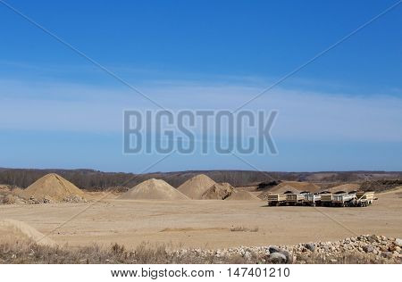 Construction equipment with a row of tractor trailers and a loader at a industrial gravel pit yard site