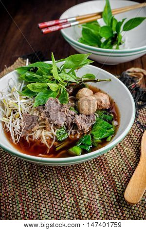 asian noodle soup with beef meatball with fresh vegetable on wood table vintage style street food hot and spicy noodle soup asian food