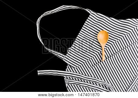 Closeup of kitchen utensils in pocket of apron on white table