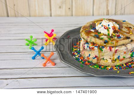 Cookie ice cream sandwich on pewter plate with colorful toy jacks on wood
