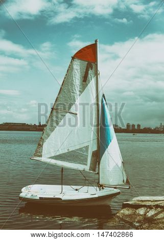 Small sail yacht moored near the shore