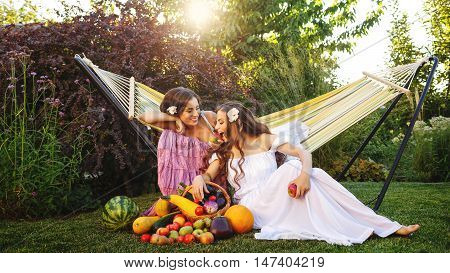 Two cute sisters resting after harvesting. Ripe fruits and vegetables. A bountiful harvest. Agriculture.