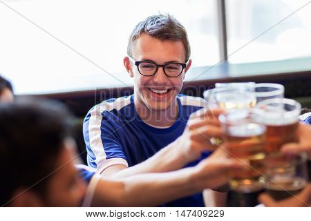 sport, soccer, people and leisure concept - happy friends or football fans s clinking beer glasses at bar or pub