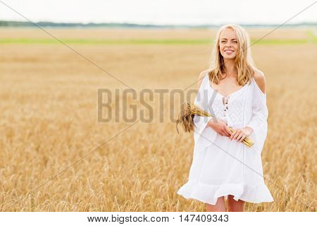 country, nature, summer holidays, vacation and people concept - smiling young woman in white dress with spikelets walking along on cereal field