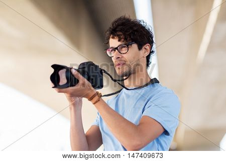 people, photography, technology, leisure and lifestyle - photographer with digital camera shooting in city