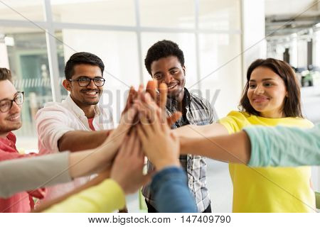 education, school, teamwork, gesture and people concept - group of international students making high five