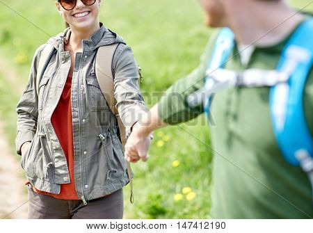 travel, hiking, backpacking, tourism and people concept - close up of happy couple with backpacks holding hands outdoors