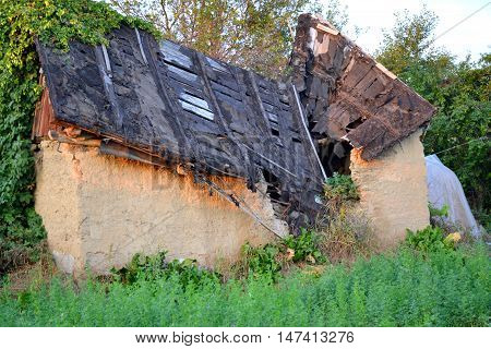 abandoned old house with the broken roof and overgrown with grass