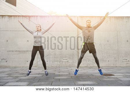 fitness, sport, people, exercising and lifestyle concept - happy man and woman doing jumping jack or star jump exercise outdoors