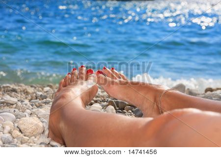 Beautiful woman feet on the beach