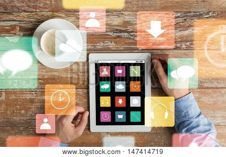 business, media, people and technology concept - close up of male hands with menu icons on tablet pc computer screen and coffee cup on wooden table