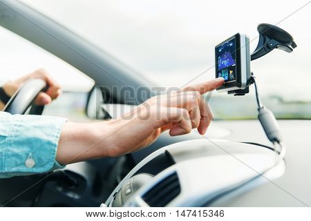 transport, business trip, technology, navigation and people concept - close up of male hand using gps navigator while driving car