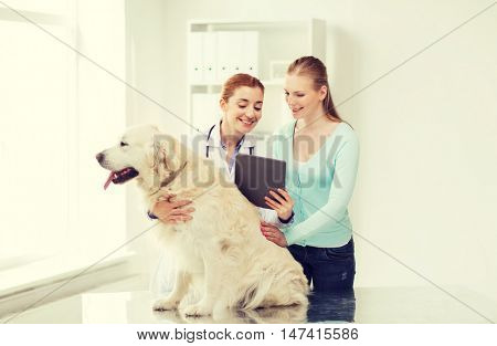 medicine, pet, health care, technology and people concept - happy woman with golden retriever dog and veterinarian doctor holding tablet pc computer at vet clinic