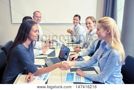 business, people, gesture and partnership concept - smiling business team with laptop computer and papers shaking hands in office