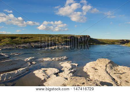 Rocky shore of the river in the tundra. Small Usa river, Polar Urals.