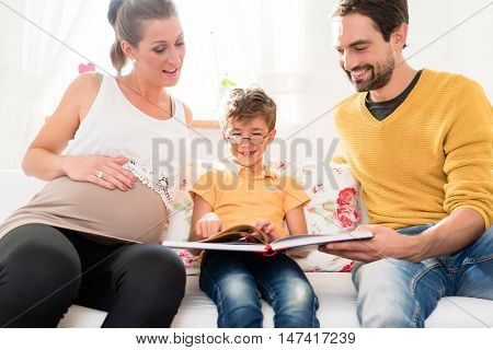 Dad and pregnant mum showing their firstborn son pictures of his own birth in family album