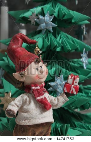 Christmas Elf Giving A Present Under Christmas Tree