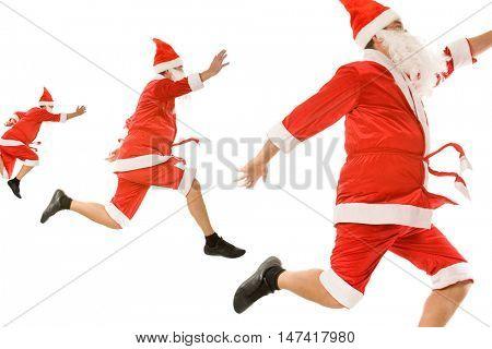 Image of three santa clauses  hurrying for xmas