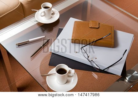 Closeup of glass table with folders, notebook, glasses, pens and cups of coffee on it