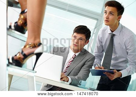 Two businessmen staring at beautiful female legs