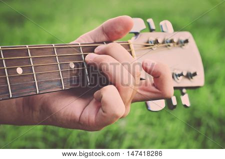 Man and guitar. Man's hand playing the guitar. Guitar Strings (vintage)