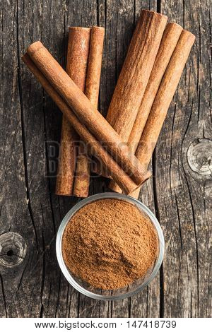 Cinnamon sticks and ground cinnamon on old wooden table. Top view.