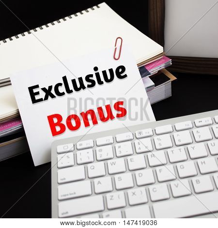 Word text Exclusive bonus on white paper card / business concept