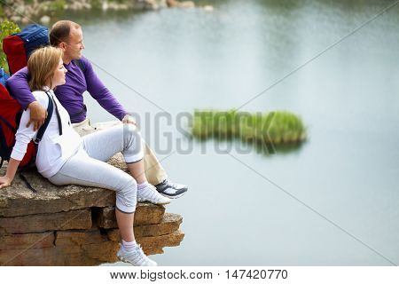 Young couple sitting on cliff and enjoying beautiful panorama