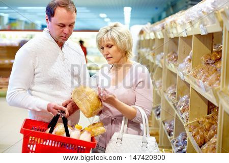 Mature couple putting bred into shopping basket