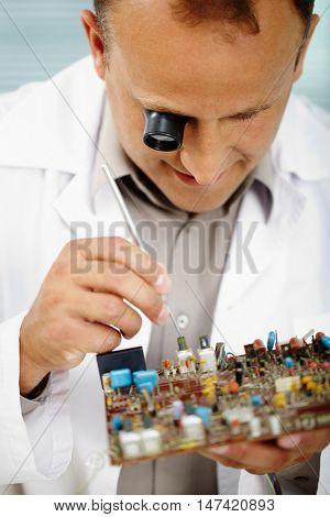 Serious engineer examining computer chip