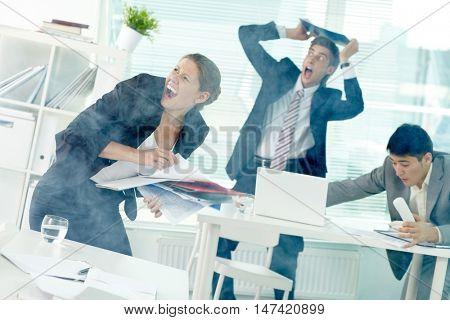 Terrified office workers screaming in office in smoke