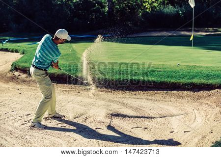 Golfer in sand trap, toned image, green, horizontal image