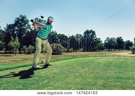 Teeing off with driver, toned image, green, horizontal image