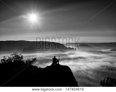 Tourist Sit On Peak Of Sandstone Rock And Watching Into Mist And Fog In Morning Valley.