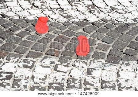 Crosswalk with red footsteps in the pavement