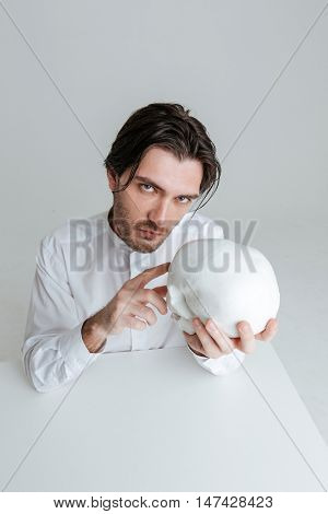 Bristled brunette man sitting at the table and pointing finger at fake skull in hands isolated on the gray background