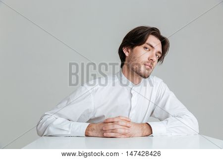 Concentrated young man in white shirt sitting at the table with fingers crossed isolated on the gray background