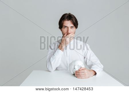 Pensive young man cover his mouth while sitting at the table and holding fake skull isolated on the gray background