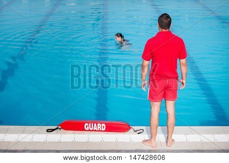 Lifeguard standing by the pool, toned image