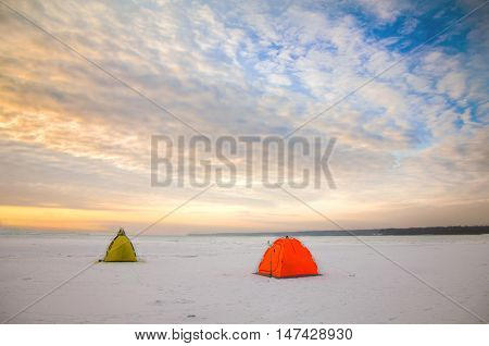 Tents camping of expedition on the ice of the Northern territory at sunset. Wild adventure tours and trekking in the harsh winters of Northern nature. Courage and fortitude of traveler.