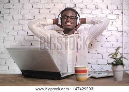 Relaxed man listening to music while sitting at his desk