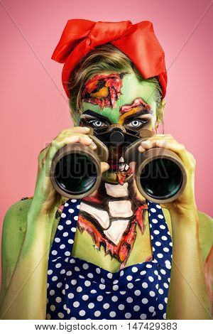 Portrait of a pin-up zombie woman looking through binoculars, pink background. Body-painting project. Glamorous zombie girl. Halloween make-up.