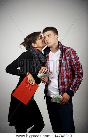 Young woman taking money from her boyfriend for shopping