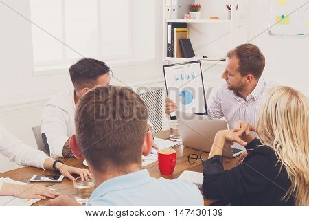 Business corporate meeting of young team. Modern businessman show diagram of company success on tablet screen in modern office. Communication with partners