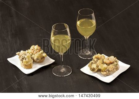 The Russian salad, served on bread in the traditional Spanish way, called ensaladilla rusa, with two glasses of white wine, on dark black background with plenty of copyspace