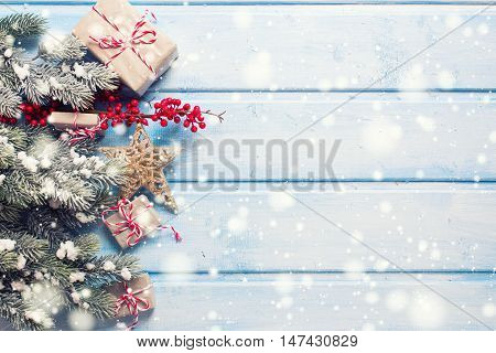 Wrapped christmas presents fur tree branches decorative star and red berries on blue wooden background. Selective focus. Top view. Place for text. Toned image.