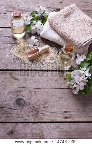 Spa or wellness setting. Sea salt bottles with aroma oil towels and flowers on aged wooden background. Selective focus. Place for text.