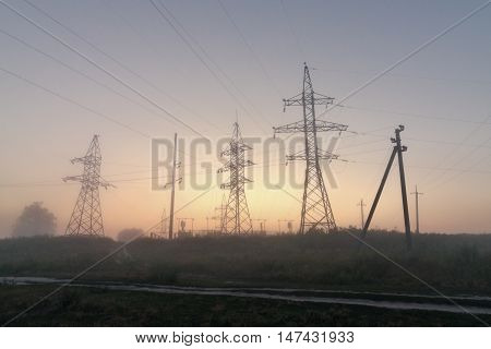 High-voltage power transmission towers in fog. High-voltage columns with wires before electric substation of the city.