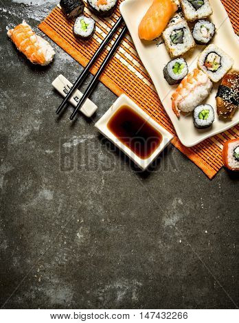 Japanese food . The rolls and sushi with soy sauce on bamboo stand.